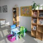 stolik dla dzieci, regał z maskotkami, regał z czasopismami, plakat z podziękowaniami od dzieci z przedszkola