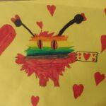 obraz przedstawia stworka z kolorową głową (różnokolorowe poziome pasy) i czerwonym ciałem; dookoła czerwone serca; stworek trzyma kartkę z narysowanymi sercami