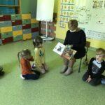 biblioterka w maseczce ochronnej czyta dzieciom w przedszkolu książkę