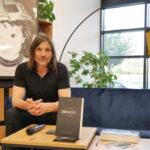 """Robert Kulik - autor książki """"Odludek"""" siedzi na kanapie""""; przed nim na stoliku widnieje jego książka, obok niej leży mikrofon; w tle duże zdjęcie w ramie przedstawiające autora w czasach dzieciństwa"""