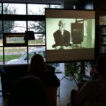 spotkanie autorskie; uczestnicy oglądają wyświetlany przez projektor film dotyczący nagrania 1128-stronicowego audiobooka przez aktora Przemysława Bluszcza