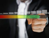 na grafice widnieje poziomy wskaźnik natężenia: po lewej kolor czerwony, który przechodzi do prawej strony w kolor zielony; za wskaźnikiem palec, który przesuwa wskaźnik ku prawej stronie