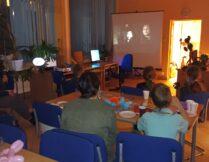 dzieci oglądają film wyświetlany na ekranie projektora