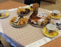 na zdjęciu widnieją ciasta przyniesione przez czytelników, a także filiżanki i talerzyki na stole przykrytym obrusem; w tle regały z książkami