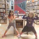 dwie dziewczynki prężą muskuły rąk na tle plakatu Nocy Bibliotek z hasłem Czytanie wzmacnia