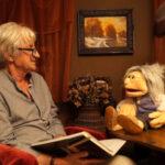 pacynka Teodozja siedzi na biurku, obok niej na fotelu siedzi pisarz i szaradzista Marek Samselski; rozmawiają o homonimach